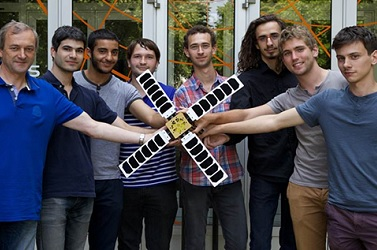 Students holding a 3D printed satellite